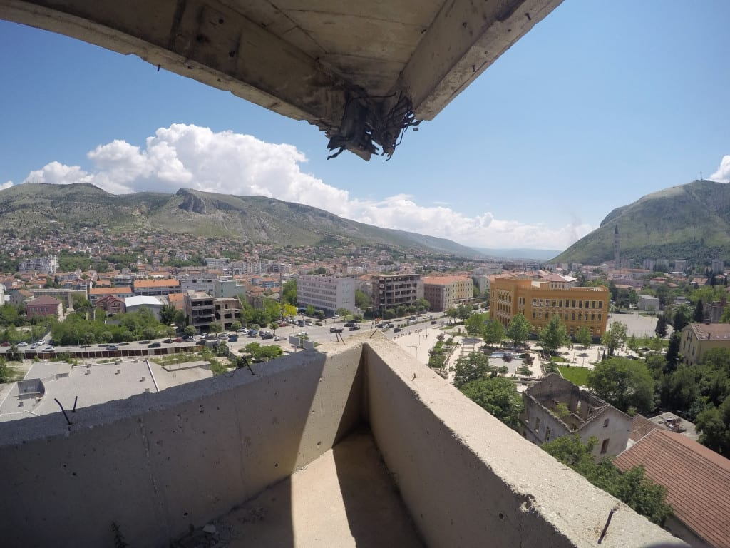 Mostar: Discovering the scars of the war that rocked Bosnia. The bombed out buildings that remain, Bosnia and Herzegovina, Bombed out buildings, sniper towner, exploring the sniper tower, how to get in, is it safe, mountains, cross, view from sniper tower, bullet holes, yugoslavia, balkan war, siege, fighting, croats, serbs, bosnians, muslims, front line, history