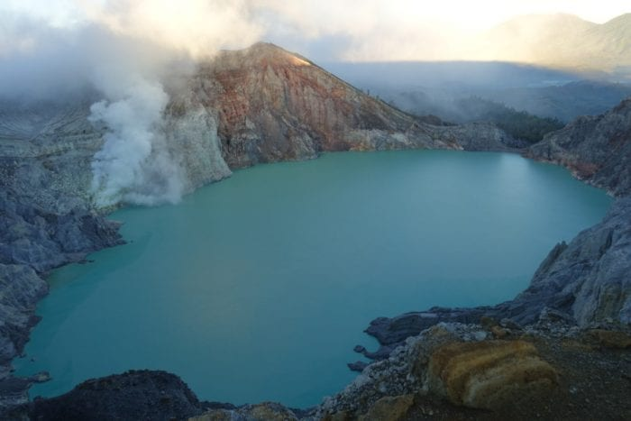 Ijen volcano hike, sunrise, Climbing the smouldering live volcano Mt Ijen in protective masks for sunrise over the sulphuric acid lake and blue flame crater, Indonesia, Karangasem, Ijen price, ijen volcano cost, Ijen volcano, Ijen Crater, Ijen volcano blue flame, blue fire, Ijen crater tour, ijen plateau, ijen volcano tour, ijen and Bromo, Ijen acid lake, ijen and Bromo tour, ijen from Bali, Ijen to Bali, Gas mask volcano, dangerous hike, most dangerous hikes, Indonesia volcano, Java, Probelingo, homestay, accommodation, Kawah Ijen, Banyuwangi, Acid lake, Blue lagoon, crater lake, acid volcano lake, volcano erupt, sulphur mining, sulphur smoke,
